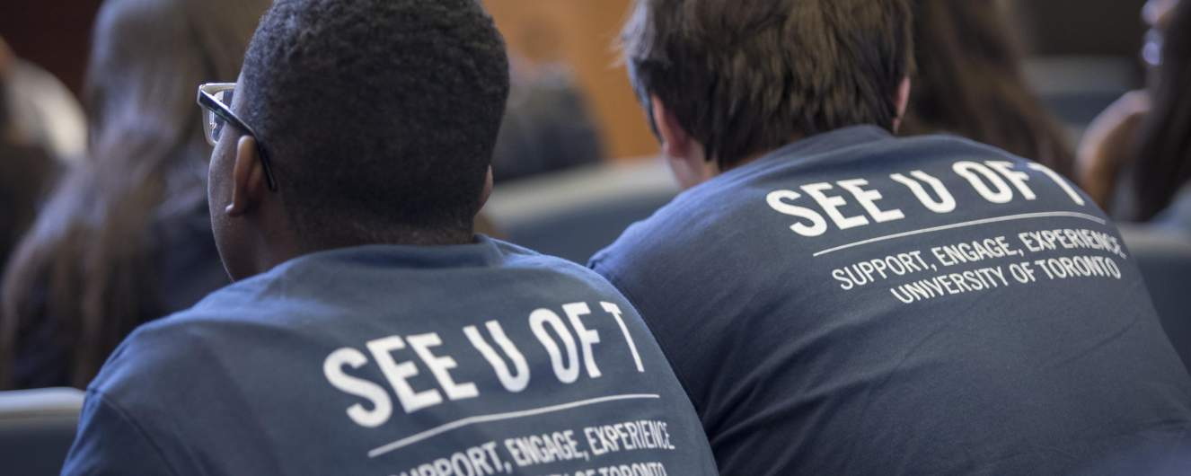 Students wearing SEE U of T t-shirts sit in class.