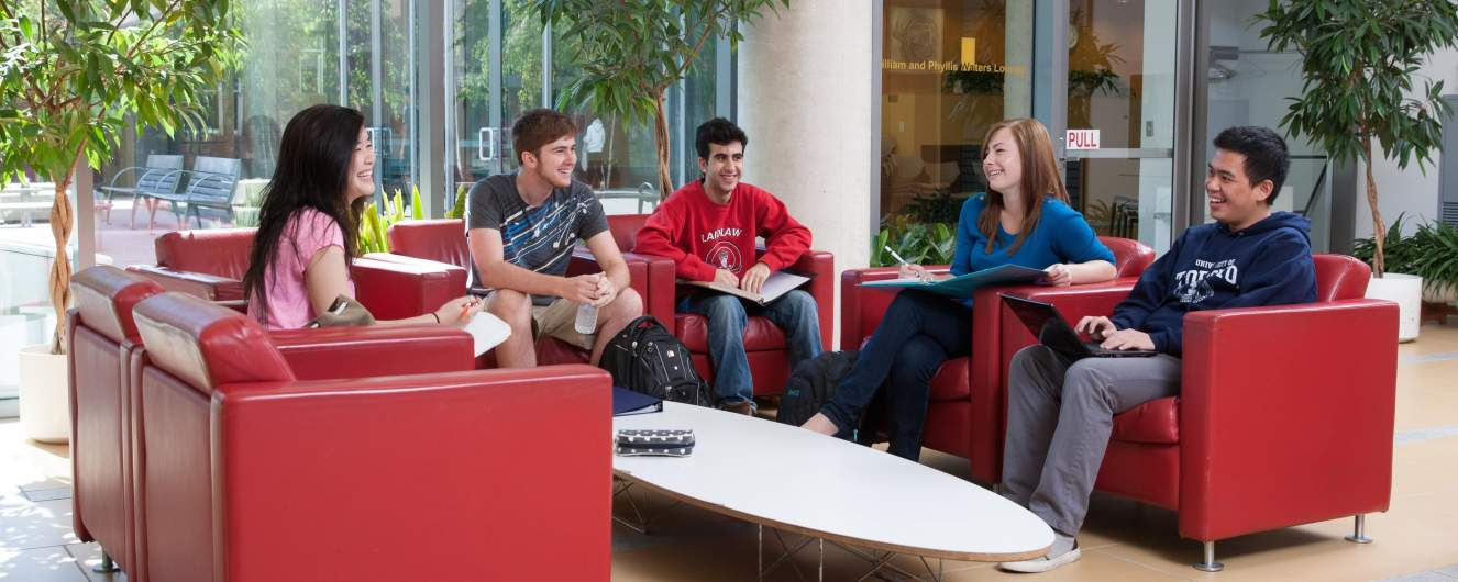 Five students chatting on the sofas in the residence lobby.