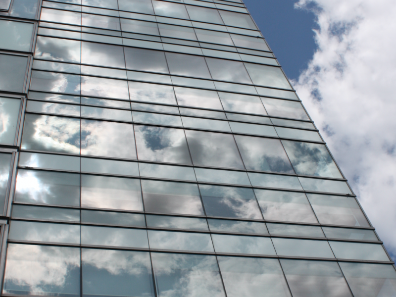 A photo of the residence tower with clouds reflected in the glass