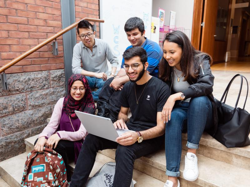 Five students sitting inside Woodsworth College looking at a laptop together and smiling
