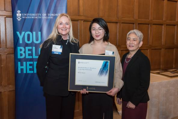 Blythe (middle) stands with Lynda Hamilton (left) and Principal Chin (right), holding her award certificate.