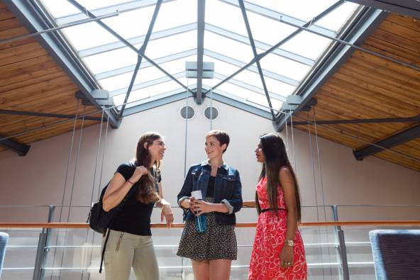 Three students talking under the skylight above Kruger Hall