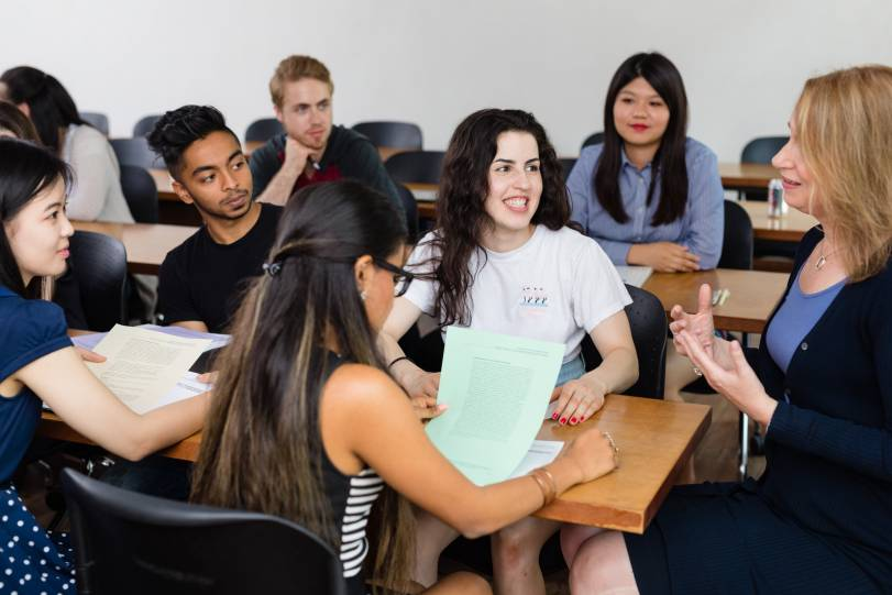 Small group of students having a discussion with an instructor in the classroom